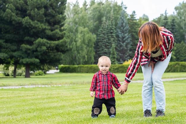 Mama pomaga swojemu małemu synowi postawić pierwsze kroki na zielonym polu w parku w ciepły letni dzień.