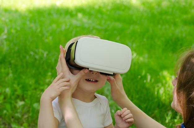 Mama poprawia synowi okulary wirtualnej rzeczywistości o ścianę zielonej trawy