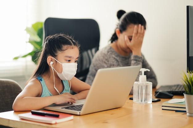 Mama pracuje w domu z dzieckiem na stole podczas pisania raportu. kobieta pracująca w domu, w izolacji kwarantannowej podczas kryzysu zdrowotnego covid-19