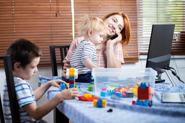 Mama próbuje pracować z komputerem przy zdalnej pracy z małymi dziećmi i rozmawia przez telefon