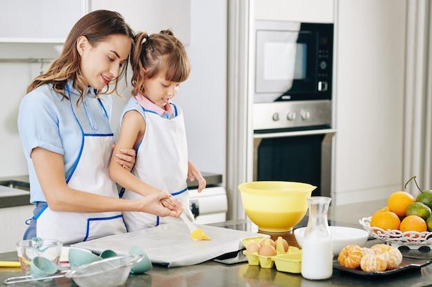 Mama prowadząca dłoń córeczki ucząc ją nakładania miękkiego masła na blachę pokrytą papierem do pieczenia
