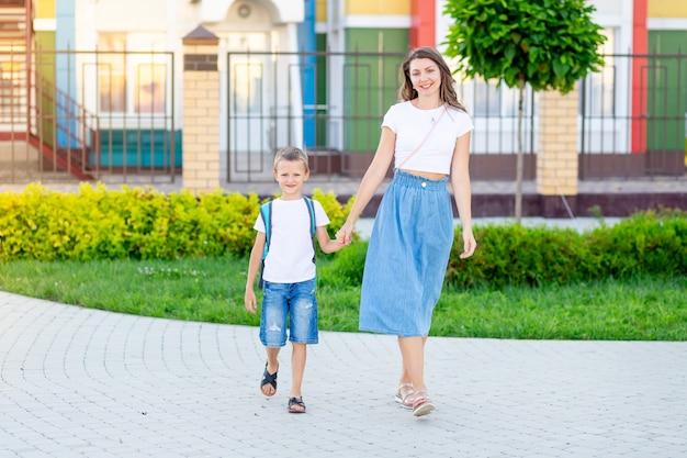 Mama Prowadzi Dziecko Syna Za Rękę Z Plecakiem Do Szkoły Lub Przedszkola I Z Powrotem Do Szkoły Premium Zdjęcia