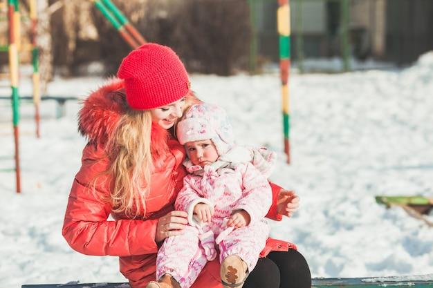 Mama przytula córkę podczas spaceru w zimowy słoneczny dzień