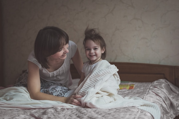 Mama przytula i bawi się z córką w chowanego na łóżku, stylu życia,