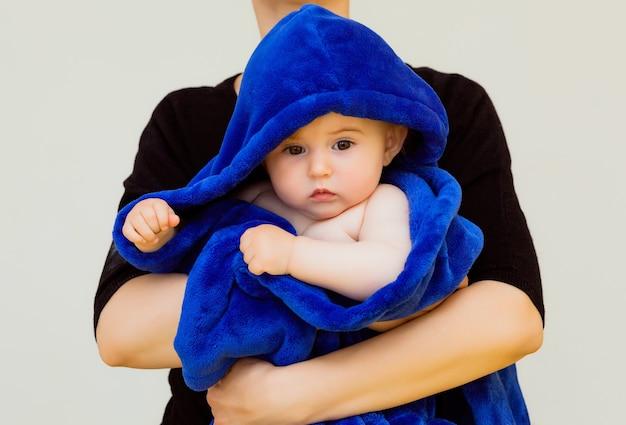 Mama przytula swoje maleństwo przykryte niebieskim ręcznikiem. matka z dzieckiem po kąpieli