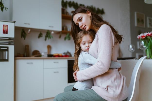 Mama przytuliła córkę w kuchni, obie twarze wyrażają cichy smutek lub smutek