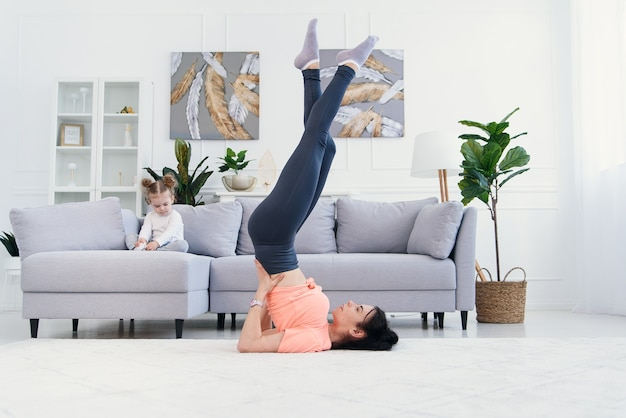 Mama robi ćwiczenia rozciągające z córeczką w domu.