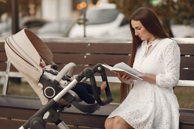 Mama siedzi na ławce. kobieta pchająca swojego malucha siedzącego w wózku. koncepcja rodziny.