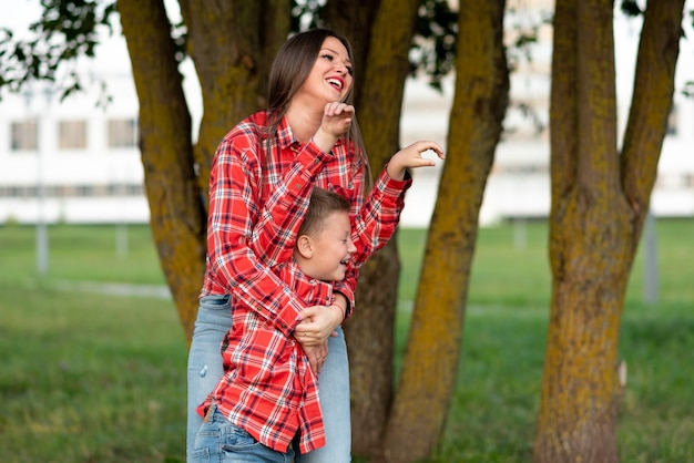 Mama śmiejąc się radośnie przytula syna, który zmrużył oczy i podniósł ręce do góry. w dowolnym celu.