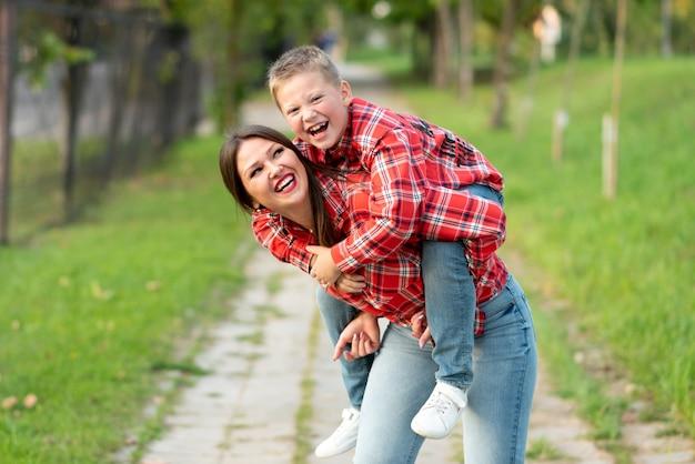 Mama, śmiejąc się, trzyma na plecach śmiejącego się syna. w dowolnym celu.