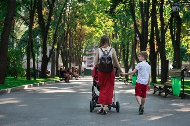 Mama spaceruje po parku z wózkiem i starszym synem. chodź z dziećmi. styl życia z dzieciństwa