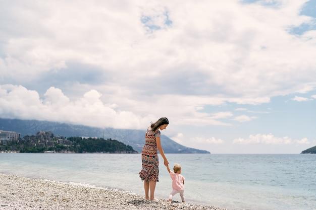 Mama spaceruje z małą dziewczynką trzymającą ją za rękę po kamienistej plaży