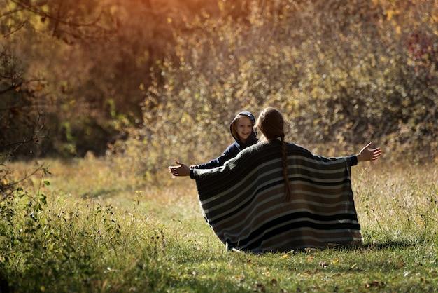 Mama spotyka biegnącego syna z otwartymi ramionami. widok z tyłu. jesień las