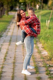 Mama szeroko uśmiechnięta trzyma syna w ramionach. w dowolnym celu.
