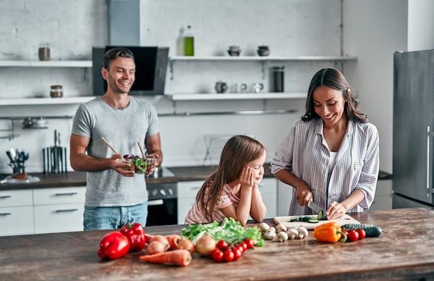 Mama, tata i córka gotują w kuchni. szczęśliwa rodzina koncepcja. przystojny mężczyzna, atrakcyjna młoda kobieta i ich śliczna córeczka robią razem sałatkę. zdrowy tryb życia.