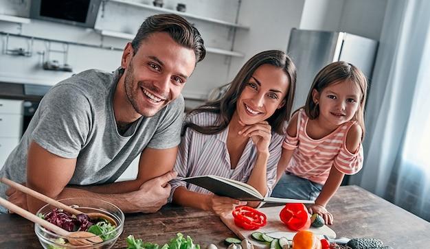 Mama, tata i córka gotują w kuchni z książką kucharską. szczęśliwa koncepcja rodziny. przystojny mężczyzna, atrakcyjna młoda kobieta i ich urocza córeczka razem robią sałatkę. zdrowy tryb życia.