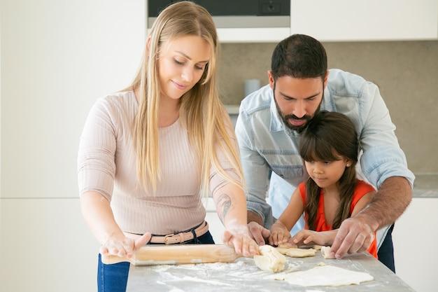 Mama, tata i córka wyrabiają i zwijają ciasto przy kuchennym stole z mąką w proszku.