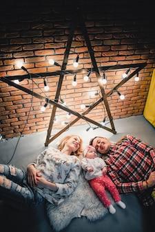 Mama, tata i dziecko leżą na wełnianym dywanie i uśmiechają się