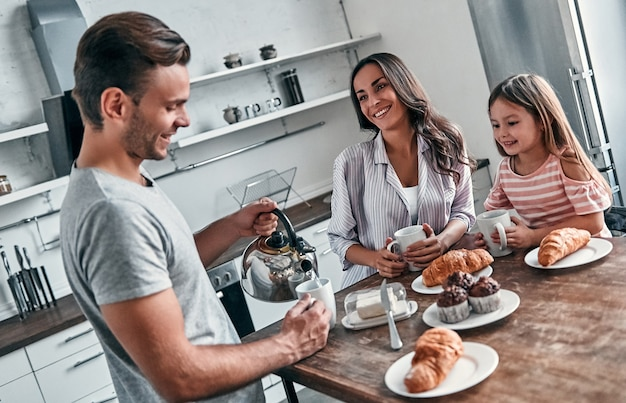 Mama, tata i ich mała piękna córeczka urządzają sobie herbatę w kuchni i rozmawiają. szczęśliwa koncepcja rodziny.