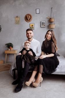 Mama, tata i mała kobieta, zabawy i przytulanie w domu na łóżku. dzień matki, ojca i dziecka. szczęśliwe rodzinne wakacje w pomieszczeniu. wygląd rodziny. szczęśliwa młoda rodzina spędzać czas razem