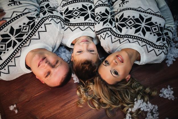 Mama tata i syn leżą na podłodze i patrzą w kamerę ubrani w identyczne swetry