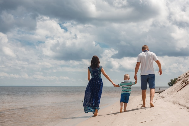 Mama, tata i syn spacery po piaszczystej plaży, trzymając się za ręce