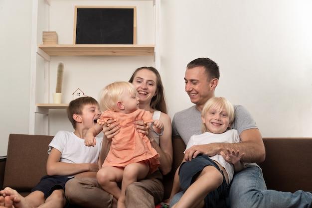 Mama tata i troje dzieci siedzą razem na kanapie. duża przyjazna rodzina.