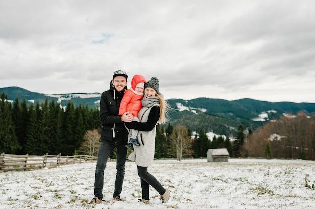 Mama, tato, dziewczyna bawią się w śnieżną zimę, spacerują po górach. ojciec, matka i córka cieszą się podróżą.