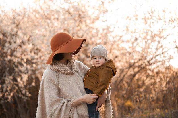 Mama trzyma dziecko na tle kwitnących drzew
