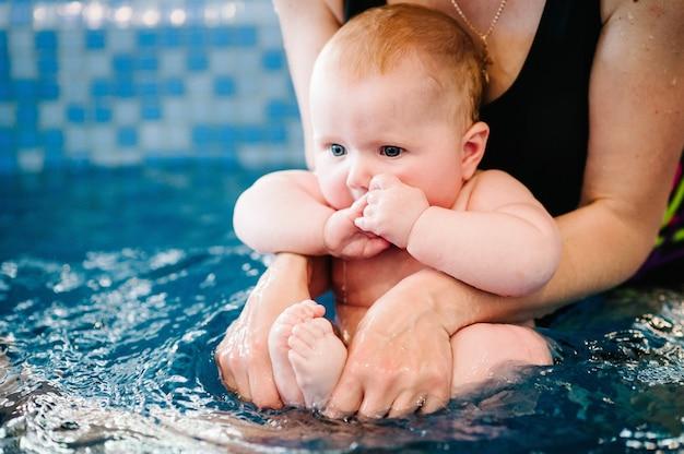 Mama trzyma dziecko przygotowuje się do nurkowania. młoda matka, instruktor pływania i szczęśliwa mała dziewczynka w basenie.