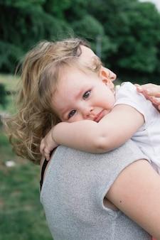 Mama trzyma małą dziewczynkę na świeżym powietrzu