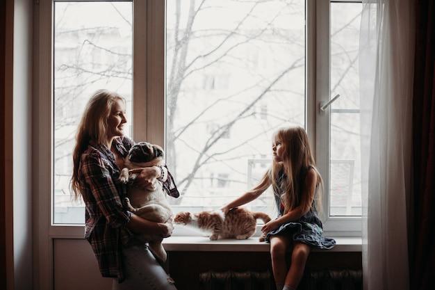 Mama trzyma psa i stoi przy oknie, dziewczyna siedzi przy oknie, w domu rodzinnym