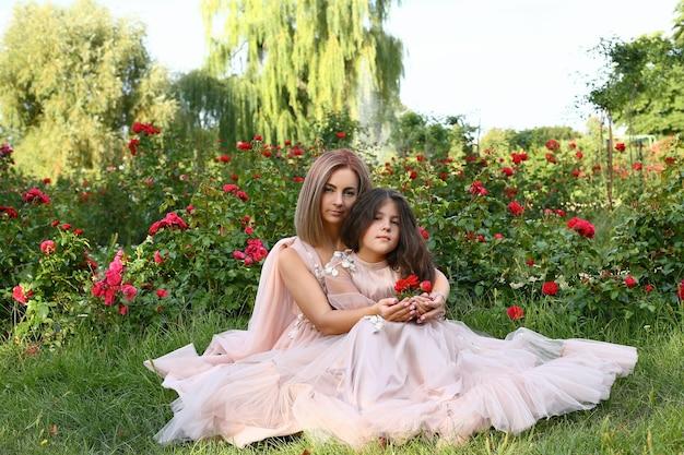 Mama trzyma rękę córki z kwiatami. zbliżenie womans i córka ręka trzyma czerwoną różę