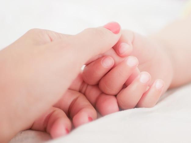 Mama trzyma rękę noworodka. zbliżenie. miejsce do pisania. umieszczanie tekstu rozogniskowanie. dziecka ręka trzyma palec mama.