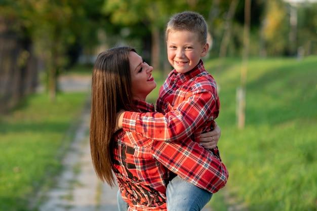 Mama trzyma syna w ramionach, oboje uśmiechnięci. w dowolnym celu.