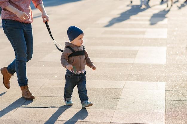 Mama ubezpiecza swoje dziecko podczas spaceru