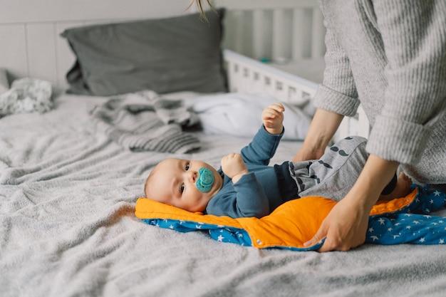 Mama ubiera ślicznego małego chłopca w kombinezon. szczęśliwa młoda matka bawi się z dzieckiem na łóżku. szczęśliwe macierzyństwo. niemowlę niemowlę.