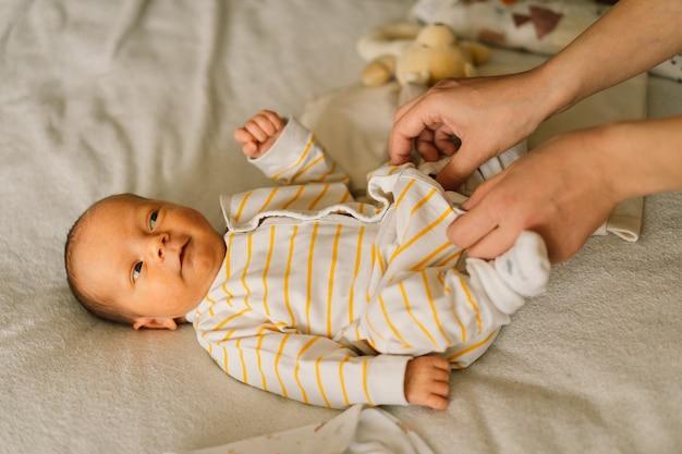 Mama ubiera ślicznego noworodka małego chłopca w kombinezon. szczęśliwa młoda matka bawi się z dzieckiem podczas zmiany pieluchy na łóżku. szczęśliwe macierzyństwo. niemowlę. dzień matki