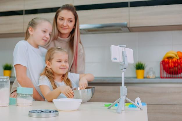 Mama uczy córki gotowania ciasta w kuchni.