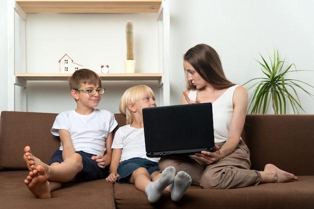 Mama uczy dwóch synów zasad korzystania z zasobów internetowych. bezpieczeństwo komputera.