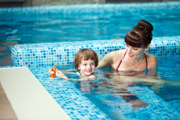 Mama uczy dziecko pływać w basenie