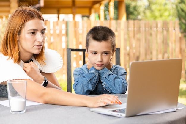 Mama uczy dziecko w domu w ogrodzie, szkolę domową. mama pomaga synowi odrabiać lekcje, stres. lekcje szkolne online za pośrednictwem laptopa