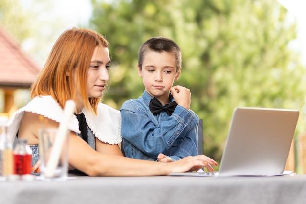 Mama uczy dziecko w domu w ogrodzie, szkolnictwie domowym. mama pomaga synowi odrabiać lekcje, stres. lekcje szkolne online za pośrednictwem laptopa