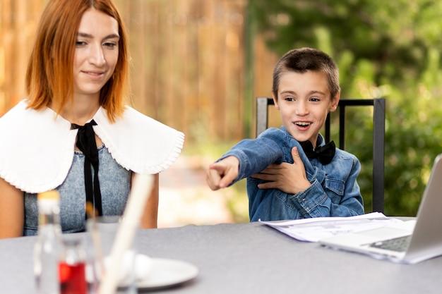 Mama uczy dziecko w domu w ogrodzie, szkolnictwie domowym. uczeń wesoło pokazuje substancje do domowych eksperymentów chemicznych. lekcje szkolne online za pośrednictwem laptopa