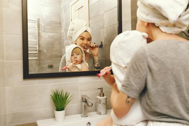Mama uczy małego syna mycia zębów