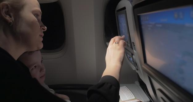 Mama uczy syna, jak korzystać z monitora siedzenia w samolocie