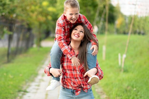 Mama uśmiechnięta niesie na ramionach roześmianego syna. w dowolnym celu.