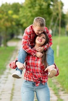 Mama uśmiechnięta niesie na ramionach syna. w dowolnym celu.