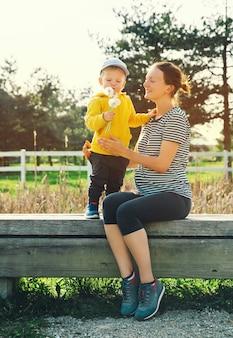 Mama w ciąży i jej syn spacerują razem i spędzają czas w parku przyrody na świeżym powietrzu