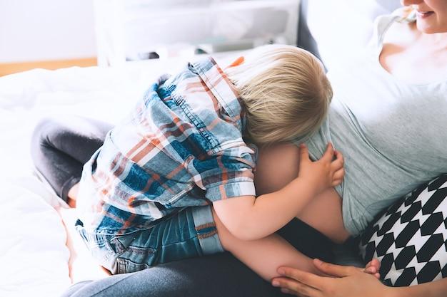 Mama w ciąży i syn rozmawiają i spędzają razem czas w łóżku w domu